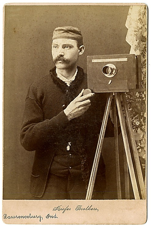 A photographer and his camera almost face forward