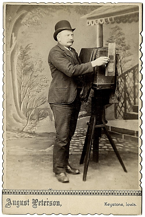 A photographer holds a masking plate or external shutter.
