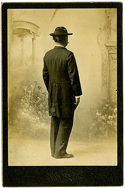 A man from the back. He wears a long jacket. A cigar is just visible