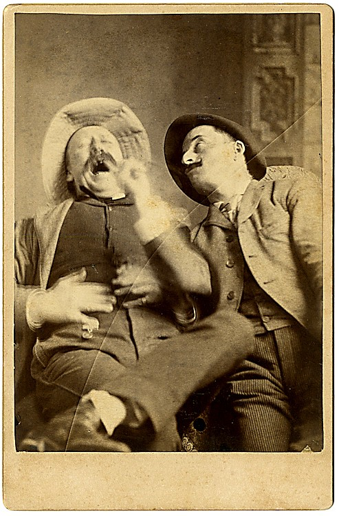 A man is in pain. Another man is sticking a finger in his mouth.