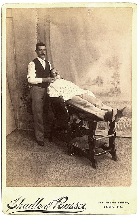 A barber shaves a customer on a reclining wood chair.