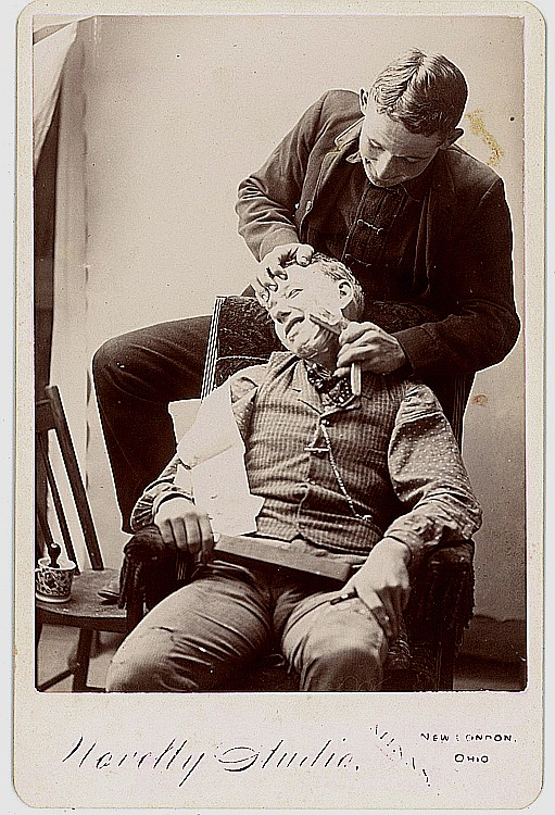 A barber shaves a customer.