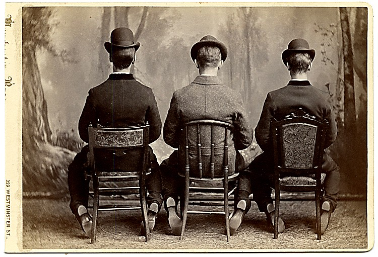 Three men from the back. They sit on different chairs.