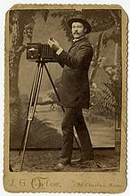 A photographer holds a small lens cap.