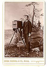 A large camera before a rich landscape backdrop.