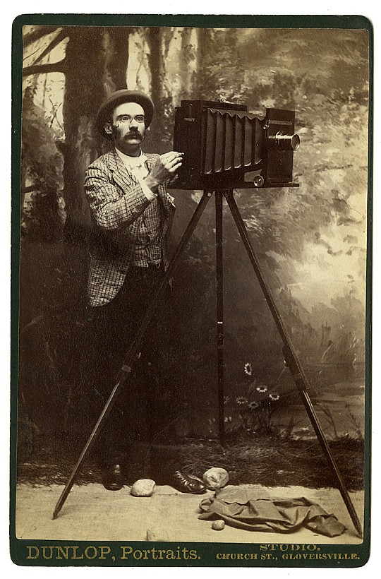 A photographer with a bellows camera, before a landscape backdrop.