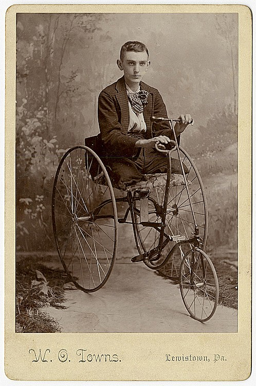 A legless man on a tricycle operated by hand levers.
