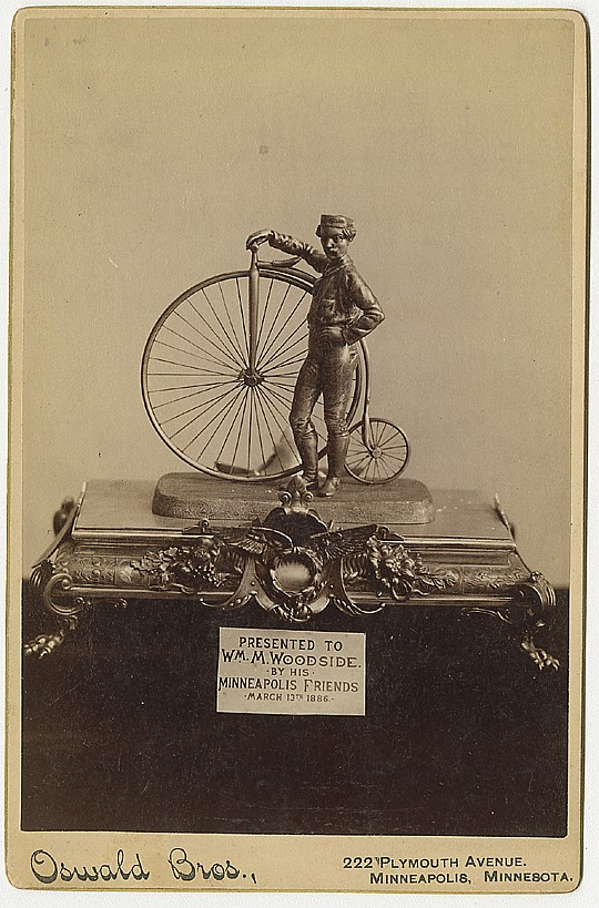 A high wheel bicycle statuette,