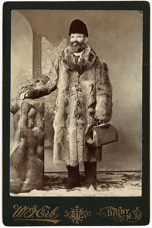 A doctor, ready to go out into the cold in his heavy coat, holding his bag.