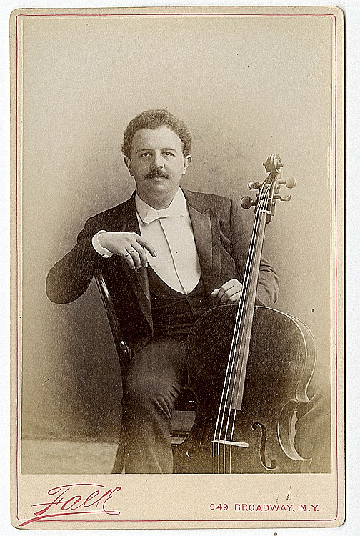 Victor Herbert, cellist and composer of many popular operettas, seated with his cello.