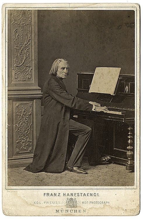 Franz Liszt, composer and virtuoso pianist seated at the piano (in the studio.)