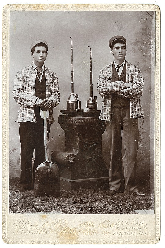 Railroad workers, with large oiling cans and a shovel for coal.