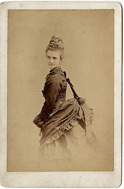 A woman with her bustle supported by a cloth attached to her shoulder.