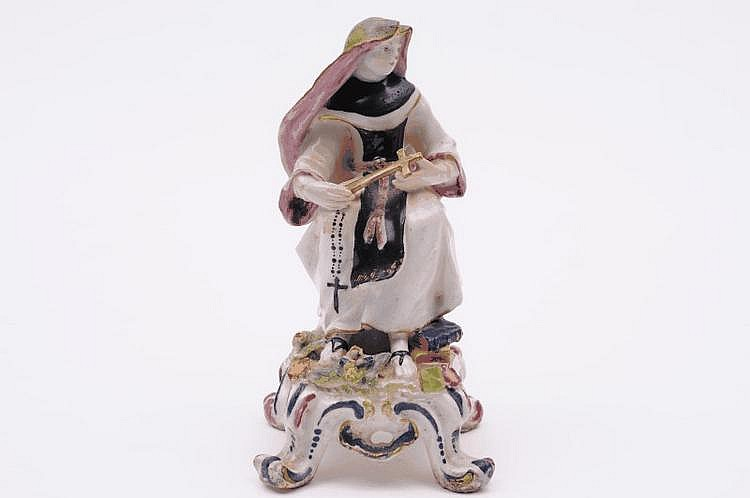 A Bow figure of a nun wearing a black, green and