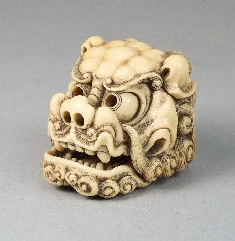 A japanese carved ivory netsuke of temple lion
