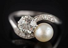 A pearl and diamond two-stone crossover ring: with