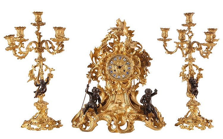 Three-piece mantel garniture. Fire-gilt and dark brown patinated bronze. Comprising a mantel clock (60 x 50 x 23) and a pair of five-light candelabra (h.: 61). Applied with putti, scrolling leaves and a couple of doves. Louis XV style. Napoleon III