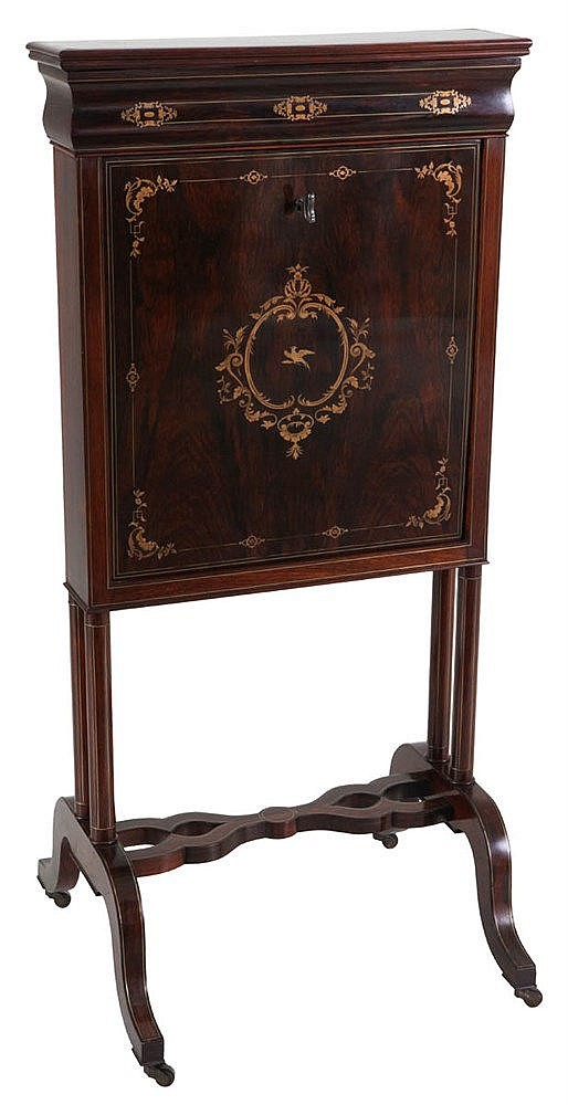 Secrétaire en portefeuille. Rosewood veneer with copper inlay. Drop front hiding three drawers, several compartments and brown leather lined writing surface. On wheels. Restauration style.