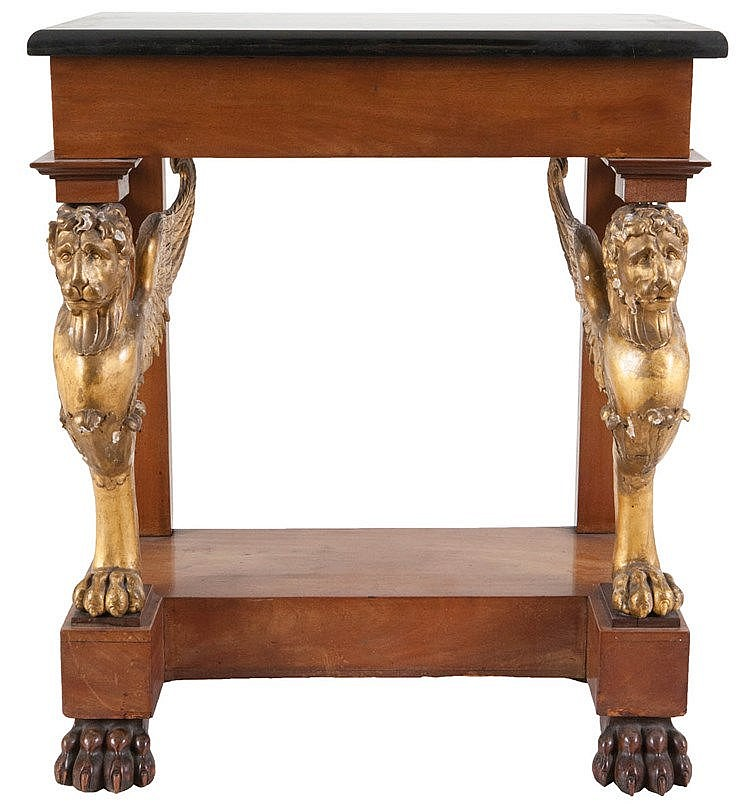 Low wall console. Mahogany veneer and gilt walnut. Posts in the shape of winged lions. On claw legs. Black marble top. Probably Scandinavian work. Around 1830.