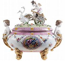 Meissen porcelain oval-shaped tureen and cover. The cover surmounted by an angel in a chariot drawn by two swans. Putto-shaped handles. Body painted with flowers. Scrolling feet. Crossed swords mark in underglaze blue.