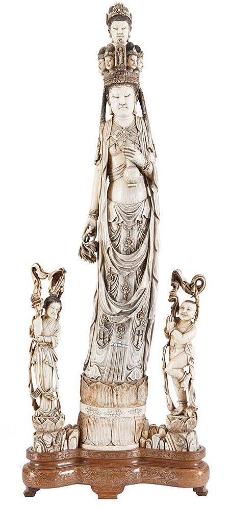 Female immortal holding a vase and branch, crown with various female heads, standing on a lotus stand, flanked by two servants. Carved ivory, partly tinted black. Chinese work, first half of the 20th century. Ironwood stand of later date.