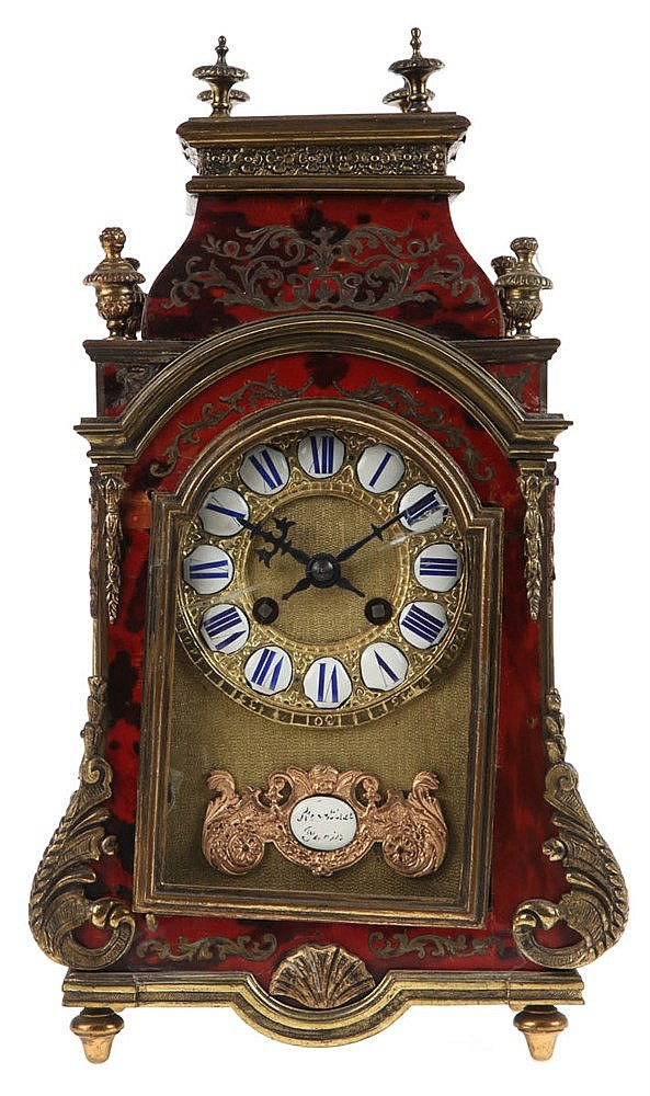 Boulle' mantel clock. Ebonised wood veneered with red stained tortoiseshell and brass inlay. Louis XVI style. Napoleon III period.