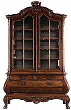 Display cabinet. Walnut and rootwood veneer. Shaped cornice. Two doors, two large and two smaller drawers. Chamfered corners. Shaped apron. Ball and claw feet. Copper handles. Carved decor of gadroons, shells, rocailles and foliage. Dutch work.