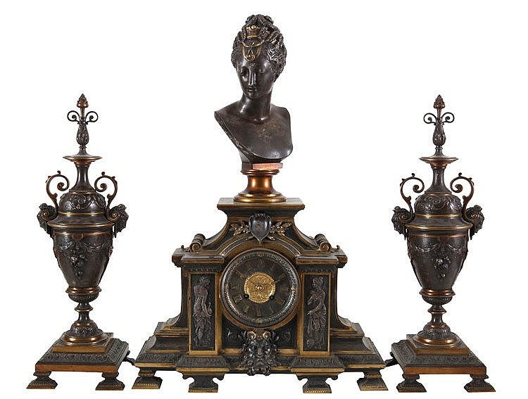Three-piece neorenaissance mantel garniture. Brown patinated and gilt bronze. Comprising a mantel clock (h.: 55) surmounted by a bust of Diane de Poitiers and a pair of double-handled vases (h.: 43). Napoleon III period.