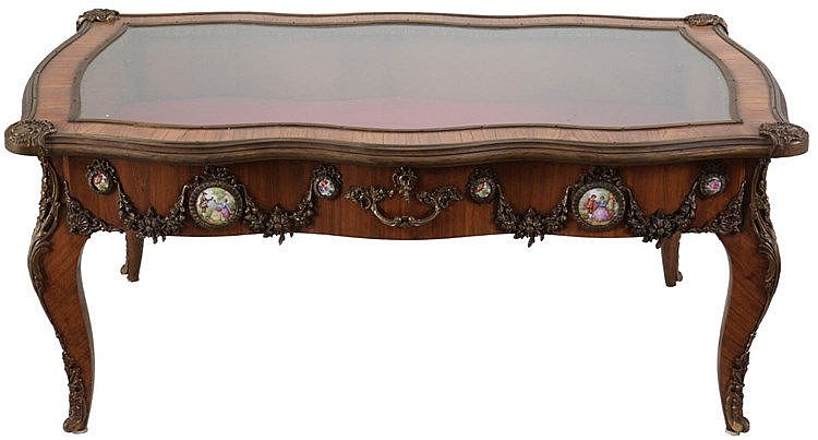 Low display table. Rosewood veneer. Set with porcelain plaques joint by gilt bronze garlands. Four cabriole legs. Glass top. Louis XV style. 20th century work.