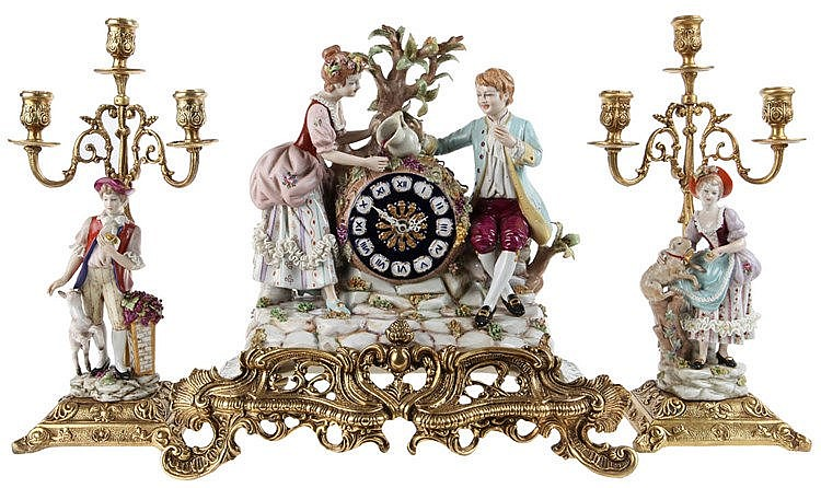 Three-piece gilt-mounted Capo-di-Monti porcelain mantel garniture comprising a mantel clock (33 x 33 x 16) and a pair of three-light candelabra (h.: 34) painted with shepherd scenes. 20th century work.