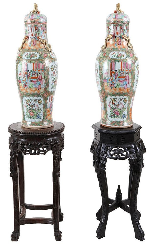 A pair of Canton Mandarin baluster vases and covers. 19th century work. One vase with hairline crack to neck. Together with two various stands, one octogonal, other with shaped rim. Chinese work (63 x 31; 62 x 35).