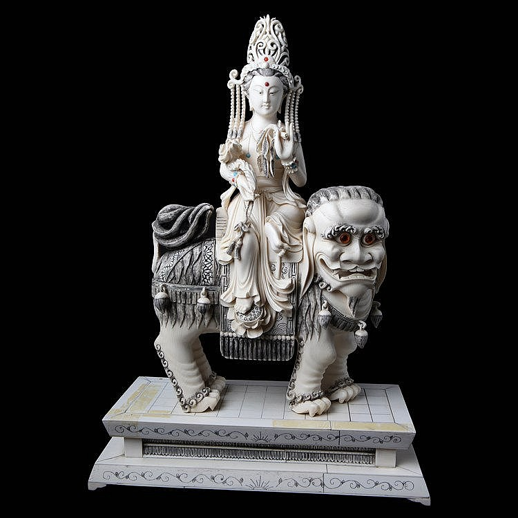 Quan'in seated on a Fo-lion. Partly black tinted ivory set with colored pearls. Wooden stand glued with ivory. 20th century Chinese work.
