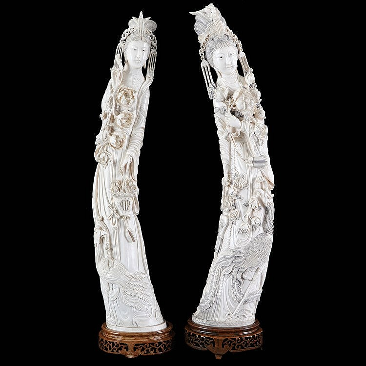 Pair of female immortals with flower basket and peony branch, flanked by a phenix. Carved ivory. 20th century Chinese work. On ironwood stands. Original boxes.