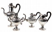 A Belgian silver four-piece coffee and tea set. Silver. Comprising a coffee, tea, sugar and milk pot. Finial in the shape of flowers, spout with foliage, gadrooned body below an engraved band of palmettes. Round foot with stylised leaves. Ebony