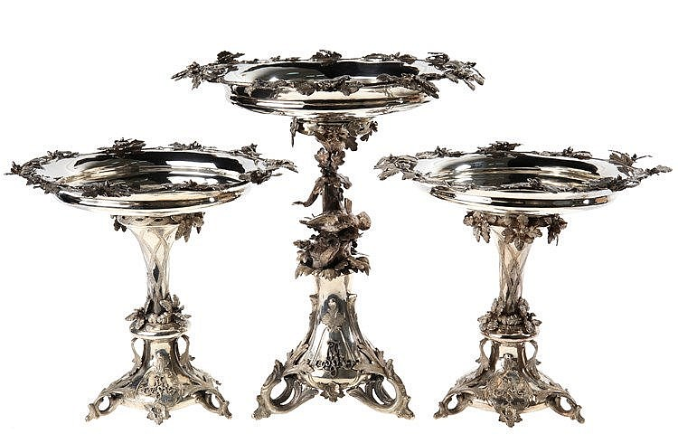 Three-part silver-plated metal center piece comprising one large and two smaller tazza on foot, one with tree trunk shaped stem with a couple of birds, others with conical stem with oak leaves. Louis XV style. Circa 1900. Detachable upper part. To be