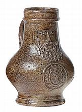 A small Cologne or Frechen so-called 'bartmannkrug' or bellarmine jug. Brown-grey glazed stoneware. Circa 1600. The globular body applied with a portrait medallion. Chip to base.