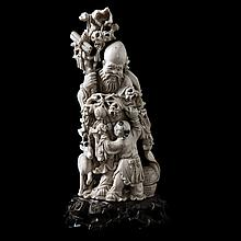 Old wiseman with staff, branch and deer flanked by a servant with bat. Carved ivory. Japanese work. Ebonised wooden stand.