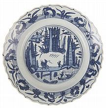Dish with barbed rim. Chinese porcelain. Wan Li period. Underglaze blue decor of a mountainous landscape with figures on a bridge at the centre and herons to the border.