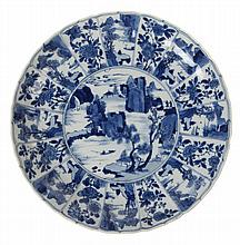 Dish with everted, slightly barbed rim. Chinese blue and white Kangxi porcelain. Depicting a water landscape with rocks in the centre surrounded by sixteen alternate fan-shaped panels of fisherman and flowering sprig. Marked with incense burner in