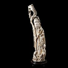 Old wiseman with dragon staff and flower branch standing on a rock, flanked by a servant with flower basket and a couple of goats. Carved ivory. Chinese work. Wooden stand.