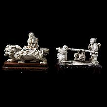 Lot of two various carved ivory figures of a standing Foo dog with puppies on its back and a couple of fruit bearers. Chinese work. Wooden stands.