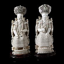 Seated emperor on dragon throne and empress on rooster throne. Carved ivory, partly set with decorative stones. Chinese work. Ironwood stands.