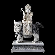 Quan'in seated on Foo dog. Carved ivory. Wooden base glued with ivory plaques. Chinese work.