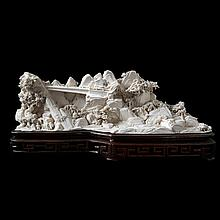 Rocky landscape with bridge, trees and figures. Carved ivory. Chinese work. On wooden stand.