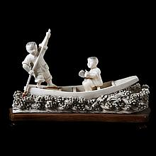 Two young fishermen in a boat on the waves. Carved ivory, partially blackened. Chinese work. Traces of glue on foot standing figure and on paddle. Wooden stand.