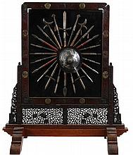 Folding screen in partially openwork stand. Ironwood frame inserted with six Japanese tsuba and four round disks. The centre inserted with a panel in black and red lacquer with on the one side a miniature shield and 24 Japanese miniature weapons and