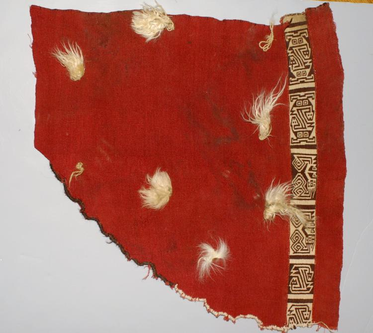 Paracas Corner section of a Red tunic with Double-faced Woven Band and Vicuna Tufts
