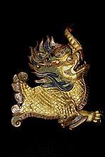 Plaque en cuivre repoussé, doré au mercure et rehaussé de polychromie, représentant un Makara, animal mythique composite, au corps et visage léonins et trompe d'éléphant, le corps flammé recouvert d'écailles. Tibet, XVIIe-XVIIIe siècles. Dim : 26 cm