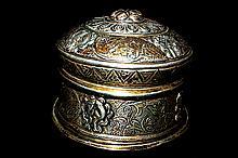 Petite boite rituelle Duphor  en argent repoussé, destinée à contenir les graines de moutarde, à décor d'objets auspicieux parmi des rinceaux feuillagés, et couronné d'une frise de lotus.  Tibet, XVIIIe siècle. Dim : 6,5 cm  60/80 €