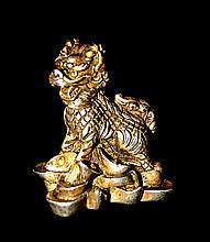 Statuette en métal argenté et doré représentant une lionne des neiges, synthèse des cinq animaux légendaires du Tibet, assise sur un tapis de neige.  Tibet, XVIIIe - XIXe siècles. Haut : 5,5 cm  250/450€